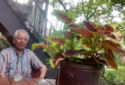 Alfonso Plasencia is relaxing at a picnic table in his backyard garden, located in East Elmhurst, 2016. Donated to Queens Memory: Memories of Migration by Walter Saavedra.