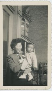 A smiling Minnie Chan holds a pouting Ellyn Chan in her arms, 1945. Donated to Queens Memory Collection at the Archives at Queens Public Library.