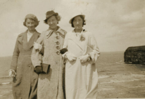 The Scanlon Sisters (left to right), Nora, Eileen, and Johanna dressed in their best take to the coast of County Kerry, Ireland. The photograph was taken after the Easter Rising in Ireland.